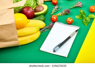 Shopping list, recipe book, diet plan. Grocering concept. Full paper bag of different fruits and vegetables,  ingredients for healthy cooking.  Diet or vegan food, vegetarian. Flat lay