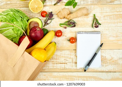 Shopping list, recipe book, diet plan. Grocering concept. Full paper bag of different fruits and vegetables,  ingredients for healthy cooking on a wooden background. healthy food.  Diet or vegan food,
