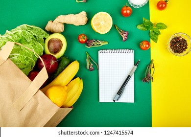 Shopping list, recipe book, diet plan. Grocering . Full paper bag different fruits and vegetables,  ingredients healthy cooking on a color background. healthy food.  Diet or vegan food, vegetar