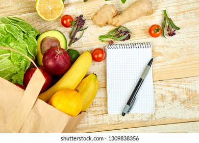Shopping list, recipe book, diet plan. Grocering concept. Full paper bag of different fruits and vegetables,  ingredients for healthy cooking . healthy food.  Diet or vegan food, vegetarian. Top view.