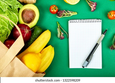 Shopping list, recipe book, diet plan. Grocering concept. Full paper bag of different fruits and vegetables, ingredients for healthy cooking. healthy food. Diet or vegan food . Top view. Flat lay.
