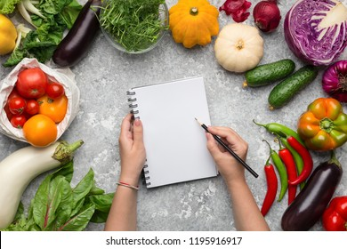 Shopping list. Woman writing in blank notebook in fresh vegetables frame, top view, copy space