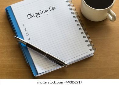 Einkaufsliste auf Notebook mit Tasse Kaffee, Planung konzeptuell