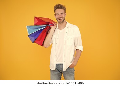 Shopping makes him feel better. Handsome man smiling with shopping bags on yellow background. Happy shopper holding colorful paper bags after shopping. Its fun to go shopping.