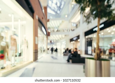 Shopping mall blur background with bokeh. Blurred hall of shopping mall with customers as background. Copy space