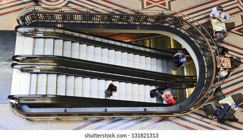 shopping mall escalator between levels for shoppers people moving down and up and sitting in cafe relaxing with coffee and newspaper