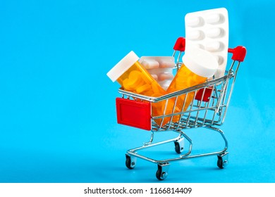 Shopping for medicines, healthcare costs and prescription medication concept with a shopping cart or trolley filled with pills isolated on a blue background with copy space