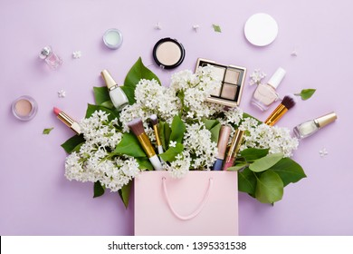 Shopping of natural woman make up cosmetics with spring white lilac bloom. Set of pring female decorative cosmetics in a pink bag on purple background. Natural organic cosmetic for makeup