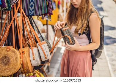 Shopping on Bali. Young woman chooses Famous Balinese rattan eco bags in a local souvenir market in Bali, Indonesia