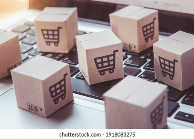 Shopping online. Cardboard box with a shopping cart logo on laptop keyboard. Shopping service on The online web. offers home delivery