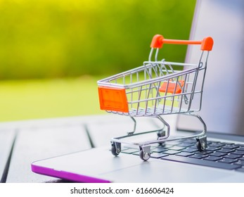 Shopping Online Concept : Mini Shopping Cart On Laptop