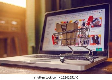 Shopping online concept - Parcel or Paper cartons with a shopping cart logo in a trolley on a laptop keyboard. Shopping service on The online web. offers home delivery.