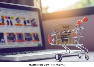 Shopping online concept - Parcel or Paper cartons with a shopping cart logo in a trolley on a laptop keyboard. Shopping service on The online web. offers home delivery
