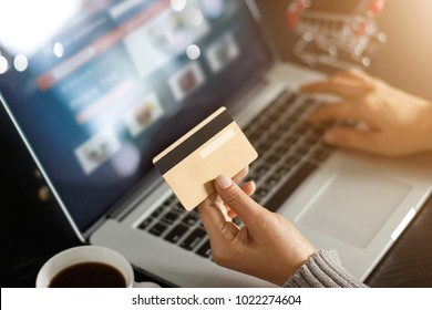 Shopping online concept. Woman holding gold credit card in hand and online shopping using on laptop at home.