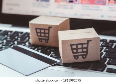 Shopping online. Credit card and cardboard box with a shopping cart logo on laptop keyboard. Shopping service on The online web. offers home delivery
