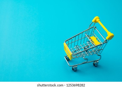 Shopping online or e-commerce modern lifestyle concept. Yellow supermarket trolley on blue background. Worldwide online shopping b2c e-commerce on internet website or social media at home.