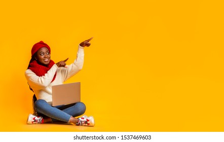 Shopping online. Young african girl in winter red knitted set with laptop pointing at copy space, panorama, yellow background