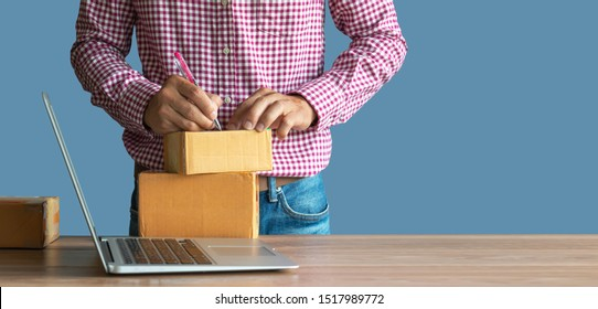 shopping online ,young start up small business owner writing address on cardboard box at workplace.small business entrepreneur SME , working with box at home, Online selling, e-commerce, packing conce