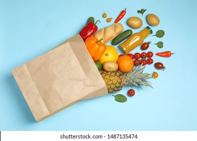 Shopping paper bag with different groceries on light blue background, flat lay
