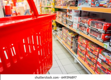 Shopping with red plastic basket in superstore. Customer browses the goods in toys department.
