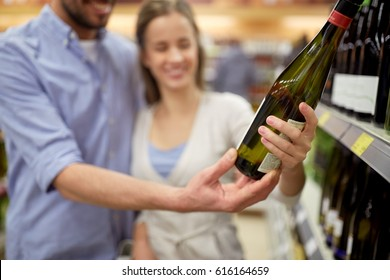 shopping, sale, consumerism, alcohol and people concept - happy couple with bottle of white wine at liquor store or supermarket