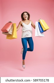 Shopping sale. Delighted woman with bags jumps up with pleasure