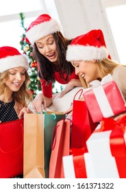 shopping, sale, gifts, christmas, x-mas concept - smiling women in santa helper hats with shopping bags and many gift boxes