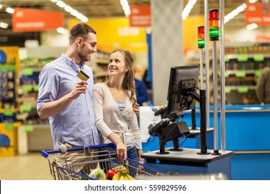 shopping, sale, payment, consumerism and people concept - happy couple with bank card buying food at grocery store or supermarket self-service cash register