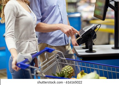 shopping, sale, payment, consumerism and people concept - couple with bank card buying food at grocery store or supermarket self-checkout