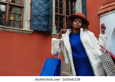 Shopping, sale, purchase concept: young fashionable woman holding shopping paper bags, posing in street. Model wearing trendy white winter faux fur coat, hat, blue dress. Copy, empty space for text
