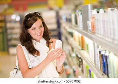Shopping - smiling woman with bottle of shampoo in supermarket