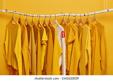 Shopping and special offer concept. Many yellow clothes items and white knitted sweater with red tag sale. Clothing shop during Black Friday. Collection of fashionable attires on seasonal sale