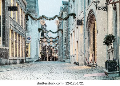 Shopping street with christmas lights and snowfall in the Dutch city center of Maastricht, The Netherlands