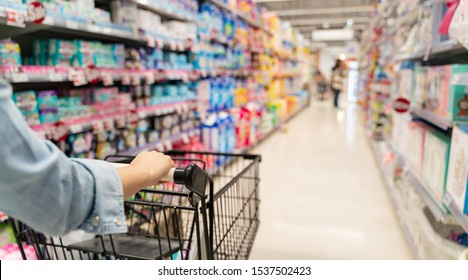 shopping in a supermarket concept.Shopping in supermarket a shopping cart view with motion blur.Close up of a woman shopping in a supermarket.Customer pushing a cart in a supermarket.