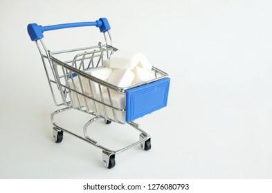 Shopping Supermarket pushcart with pile of white sugar cubes