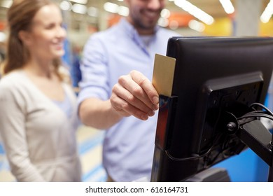 shopping, technology, consumerism and people concept - happy couple at grocery store or supermarket self-checkout swiping customer card
