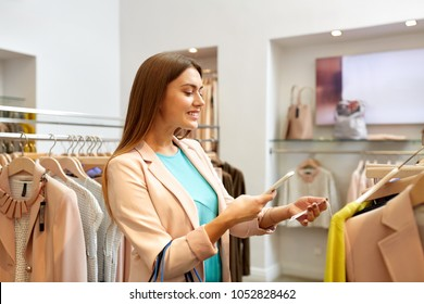shopping, technology and people concept - happy young woman choosing clothes in mall or clothing store and scanning price tag with smartphone