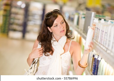 Shopping - thoughtful woman looking at bottle of shampoo in supermarket