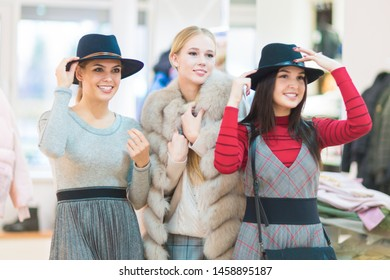 Shopping. Three Beautiful happy girls in a boutique. Try on clothes, hats.