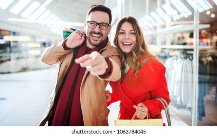 Shopping time. Beautiful loving couple enjoying in shopping, having fun together in shopping mall. Consumerism, love, dating, lifestyle concept