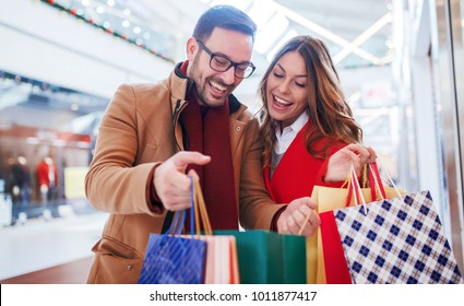 Shopping time. Beautiful young couple enjoying in shopping, having fun together in shopping mall. Consumerism, love, dating, lifestyle concept