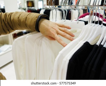 Shopping time concept. Part body buyer customer client wathing touching clothes in botique shop market.