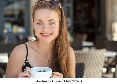 Shopping time. Happy young woman drinking a cappuccino on a terrace.