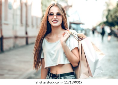 Shopping time! Happy young woman with shopping bags walking in the street.