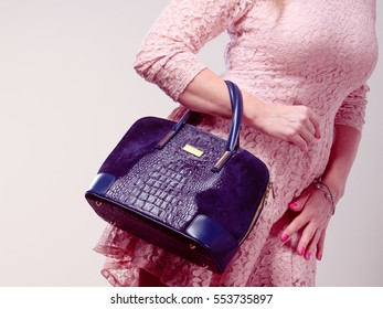 Shopping time. Part body of trendy woman wearing lovely lace pink dress. Lady with elegant black bag handbag.