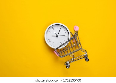 Shopping time. Supermarket trolley with clock on a yellow background. Minimalism. Top view