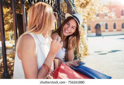 Shopping time. Two beautiful women enjoying in shopping, having fun in the city. Consumerism, shopping, lifestyle concept