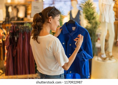 Shopping time - Young beautiful woman is holding blue jacket in her hands and looking at the price.- Consumerism, shopaholic and lifestyle concept