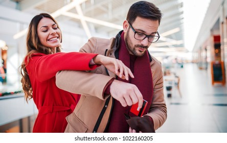 Shopping time. Young couple shopping together in shopping mall. Consumerism, love, lifestyle concept