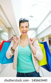 Shopping time, young woman at mall with bags, winking and smiling